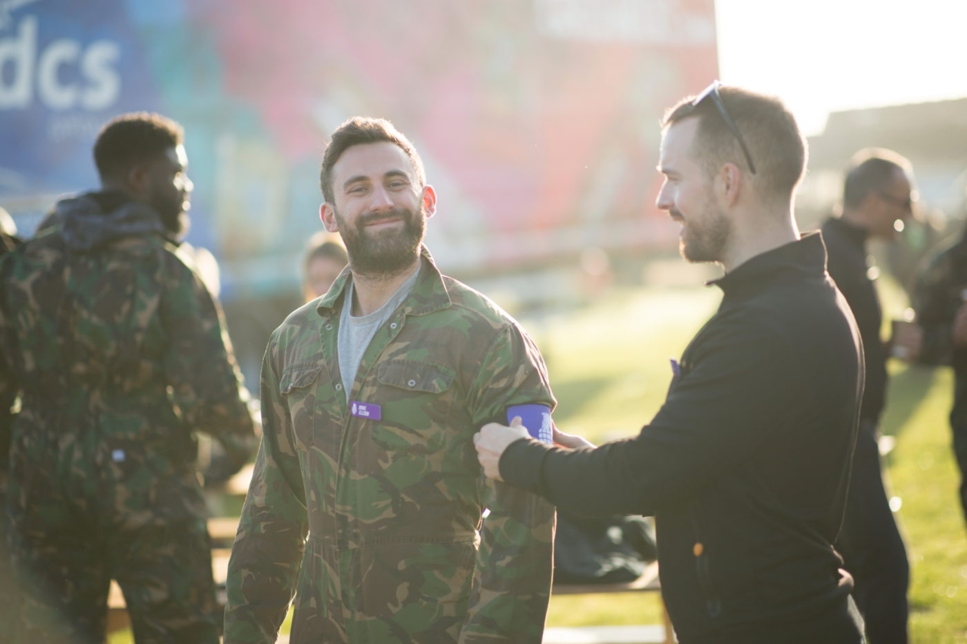 A man helps another man put on a military-style armband signifying his team colours for an activity day. Both men are smiling.
