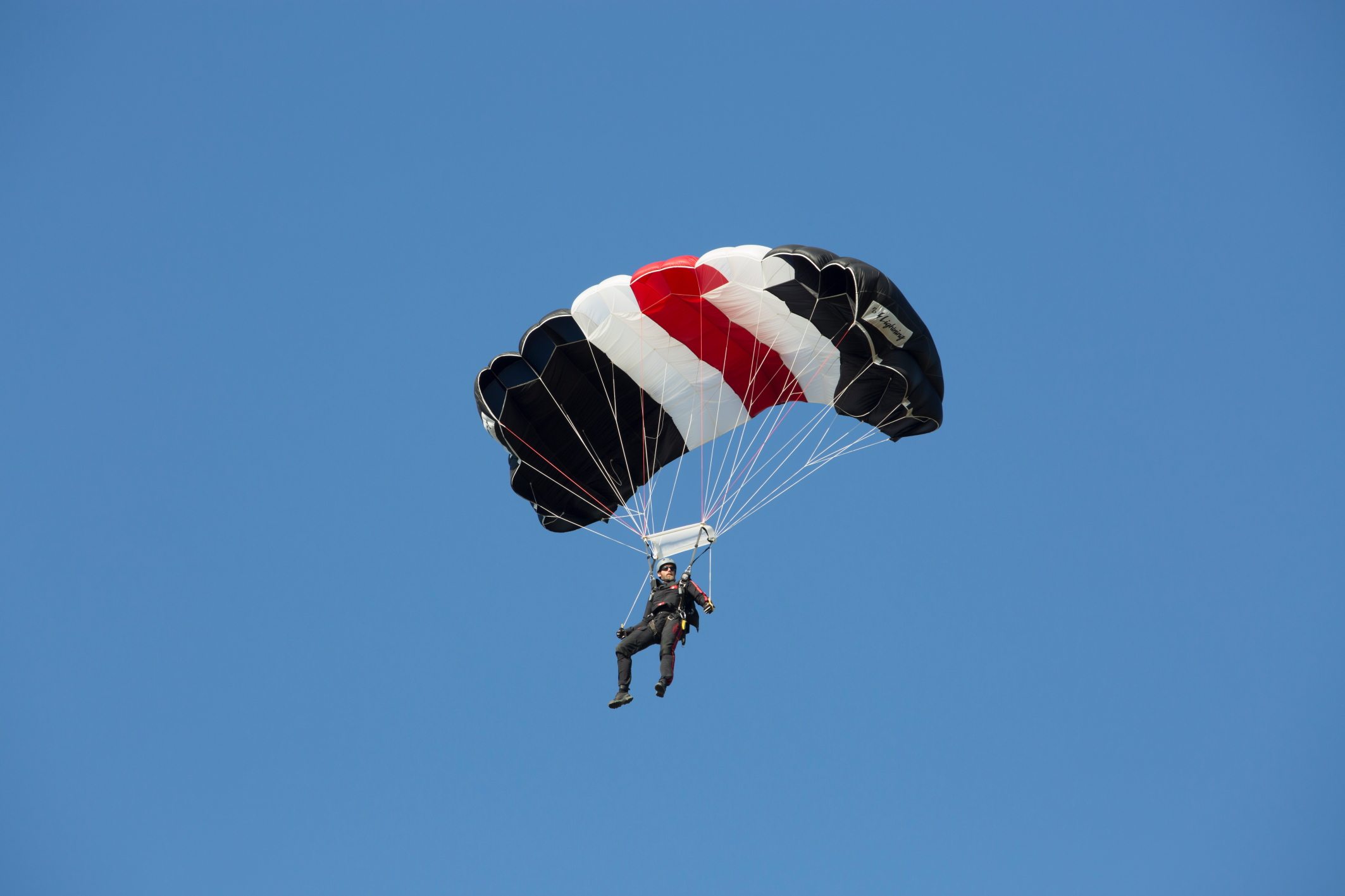 A man steers his parachute across the clear sky