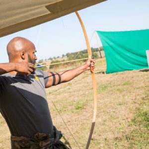 A man tries archery at a shooting range; he takes aim, pulling back on the bow just before the arrow is about to be released