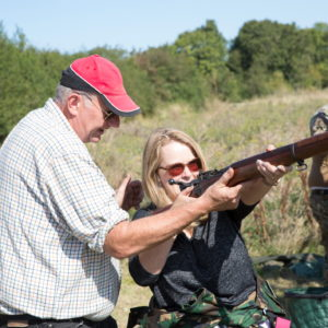 A man instructs a woman how to shoot a rifle on a firing range