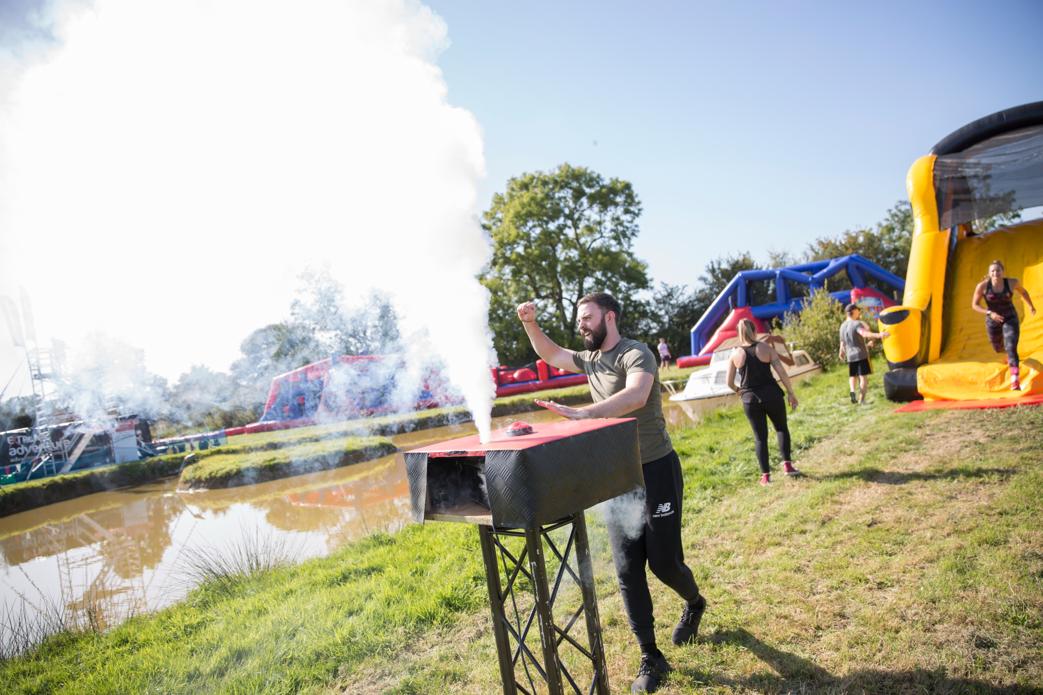 A man releases smoke plumes into the air by pushing a big button signifying his successful completion of a difficult obstacle course race. He is smiling and pumping his fist into the air in celebration.