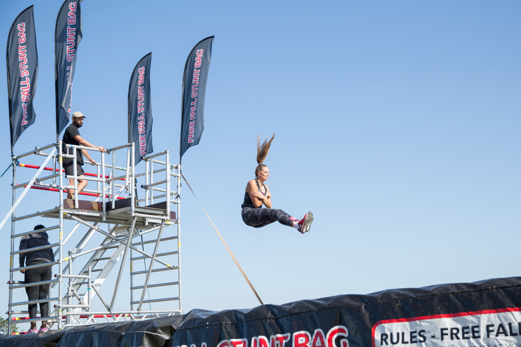 A woman jumps from a very high scaffolding tower onto a giant inflatable stunt bag below. Her pony tail stands straight up from her head as she falls through space