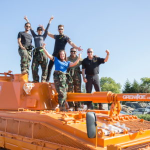 A group of people pose on top of a custom-painted orange tank bearing the Grenade logo along the gun barrel. They are smiling, their arms raised in celebration
