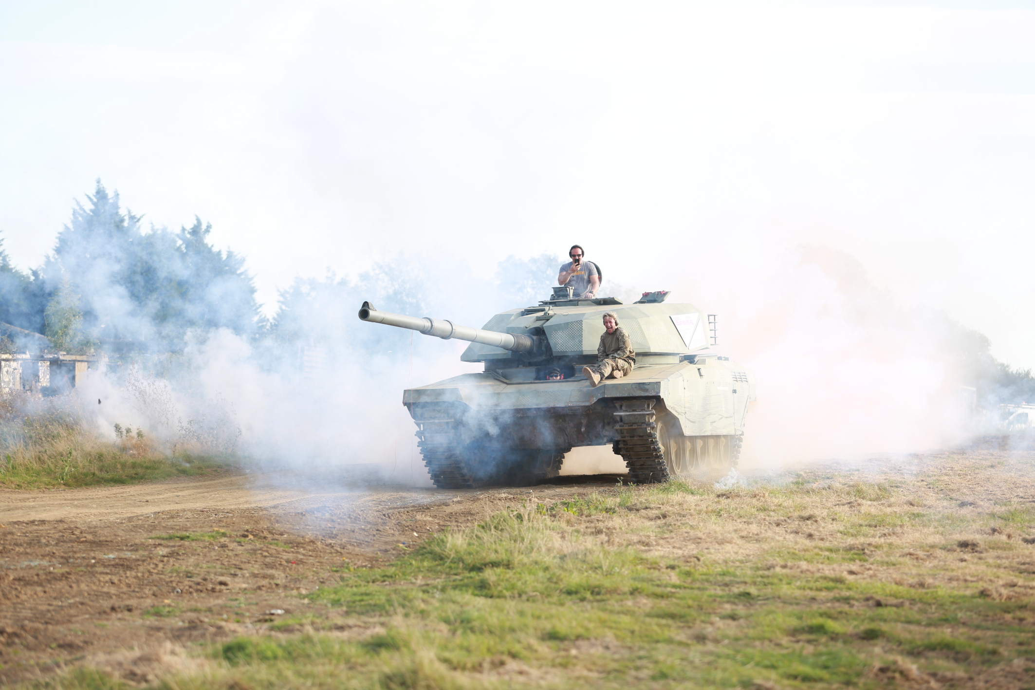A tank is driving towards camera through an atmospheric, smoke-filled field