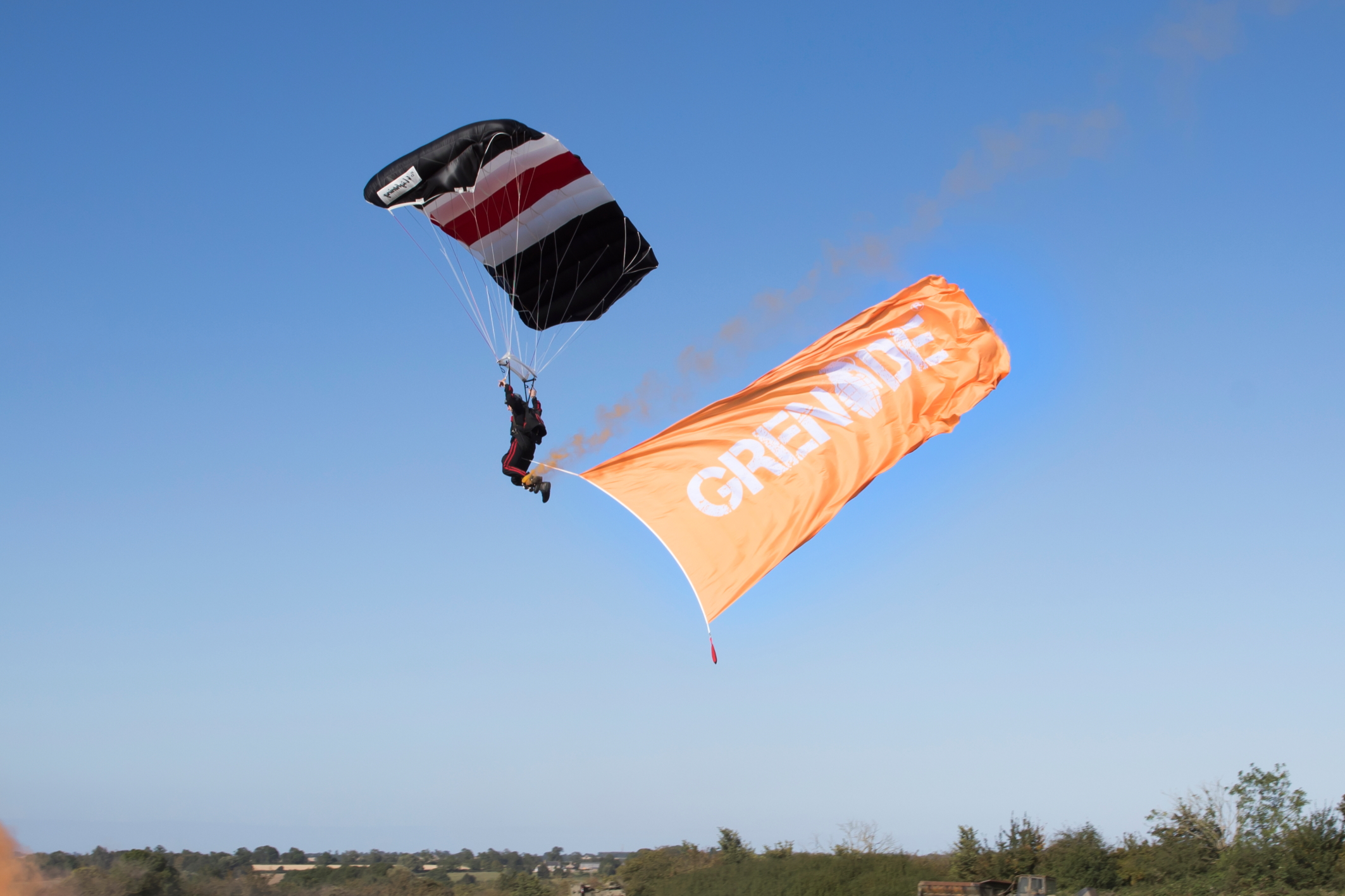Parachute jumper coming into land, trailing giant orange Grenade-branded flag