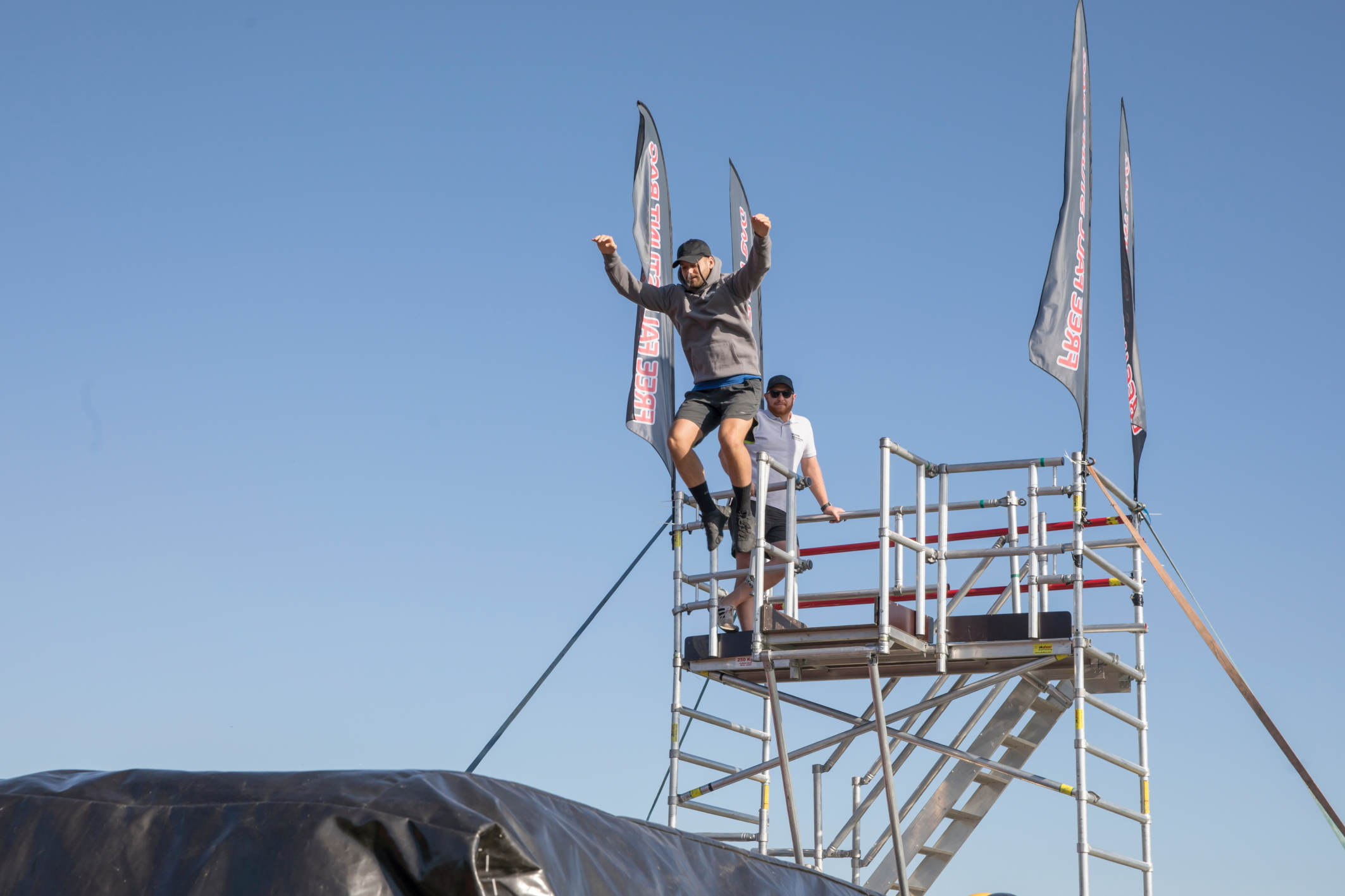 A man leaps from a very high scaffolding tower onto a giant inflatable stunt bag below