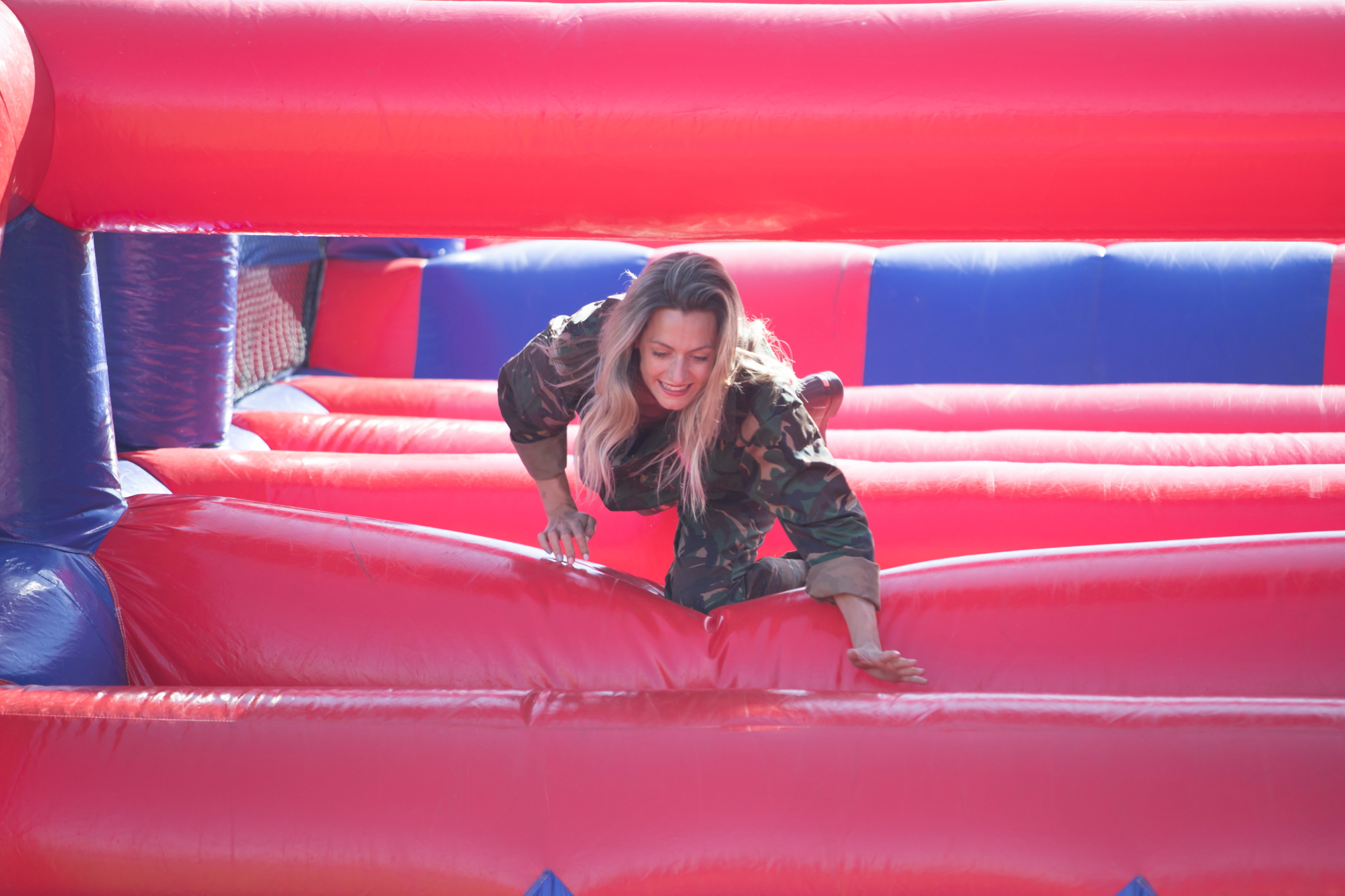 A determined woman crawls through a giant inflatable obstacle course