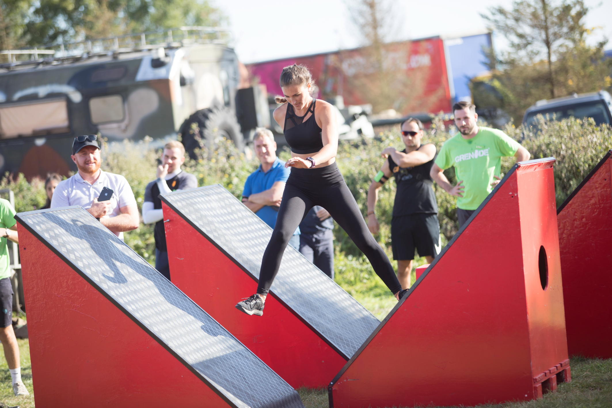 A fit woman jumps sideways between giant, angled steps as part of an obstacle course