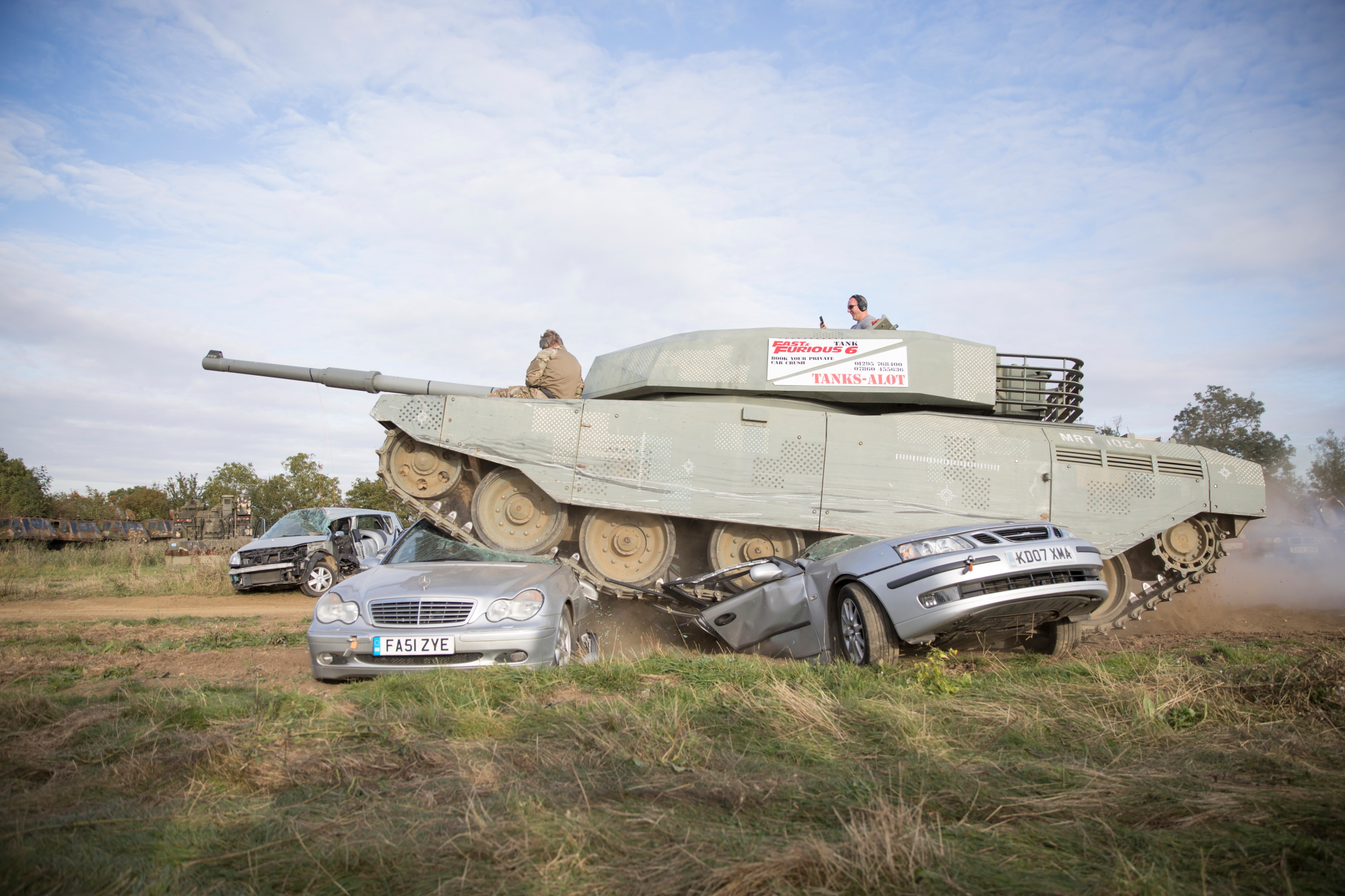 A tank drives over 2 cars, crushing them underneath them beneath the caterpillar tracks