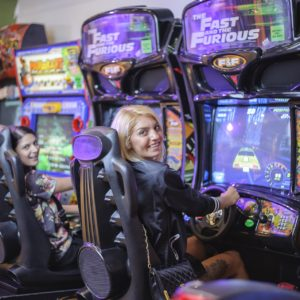 Two women, sitting at arcade driving games, look back over their shoulder and smile to camera