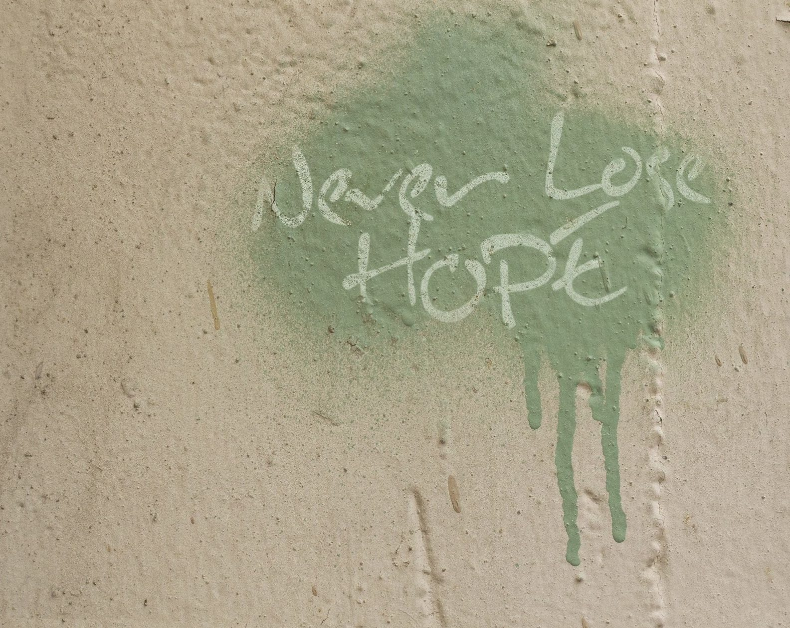 "Graffiti spray paint reveals the words, ""Never Lose Hope"" in sarcastic reference to inspirational quotes often found in the workplace"