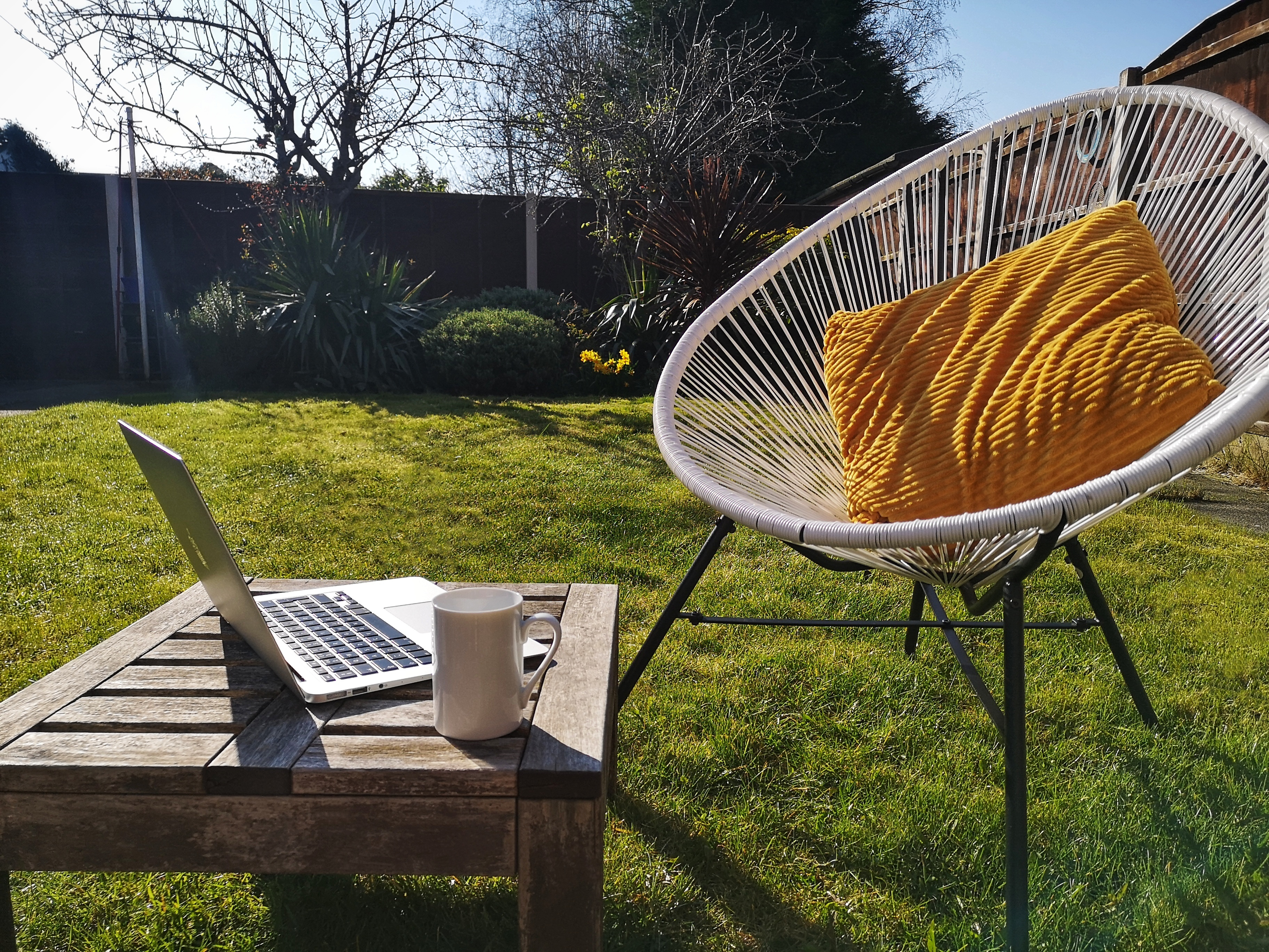 Working from home - Small home office set up in a sunny garden, laptop and coffee cup on the table beside a white chair with a yellow cushion.