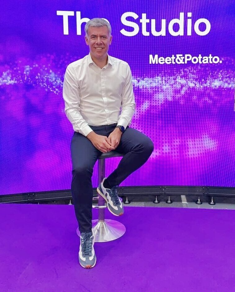 Male presenter sits on stool in front of LED screen backdrop at professional TV studio
